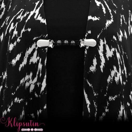 Napittoman neuletakin ja villatakin pidike nimeltä Klipsutin Mai. Kuvassa näkyy tuote käytössä.