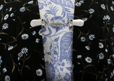 Napittoman neuletakin ja villatakin pidike nimeltä Klipsutin Sulka. Kuvassa näkyy tuote käytössä.
