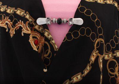 Napittoman neuletakin ja villatakin pidike nimeltä Klipsutin Helinä. Kuvassa näkyy tuotteen musta vaihtoehto käytössä.