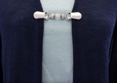 Napittoman neuletakin ja villatakin pidike nimeltä Klipsutin Helinä. Kuvassa näkyy tuotteen kirkas vaihtoehto käytössä.