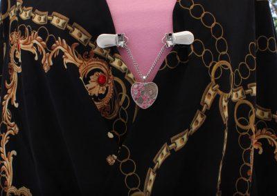 Napittoman neuletakin ja villatakin pidike nimeltä Klipsutin Rautasydän. Kuvassa näkyy tuotteen vaaleanpunainen vaihtoehto käytössä.