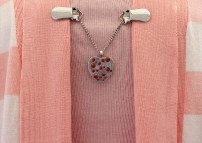 Napittoman neuletakin ja villatakin pidike nimeltä Klipsutin Rautasydän. Kuvassa näkyy tuotteen punainen vaihtoehto käytössä.