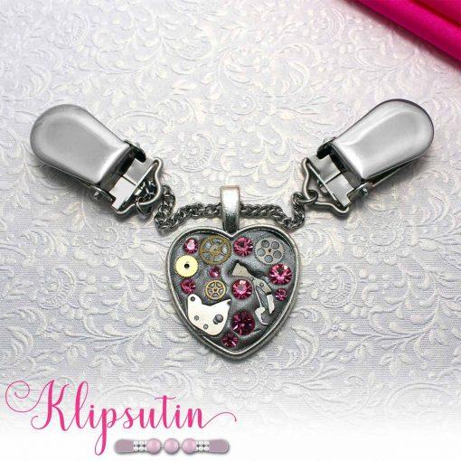 Napittoman neuletakin ja villatakin pidike nimeltä Klipsutin Rautasydän. Kuvassa näkyy tuotteen vaaleanpunainen vaihtoehto.