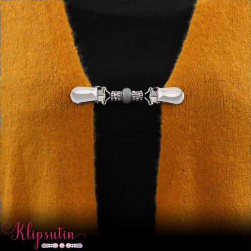 Napittoman neuletakin ja villatakin pidike nimeltä Klipsutin Veela. Kuvassa näkyy tuotteen harmaa vaihtoehto käytössä.