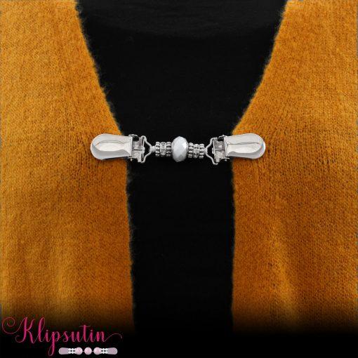 Napittoman neuletakin ja villatakin pidike nimeltä Klipsutin Veela. Kuvassa näkyy tuotteen valkoinen vaihtoehto käytössä.