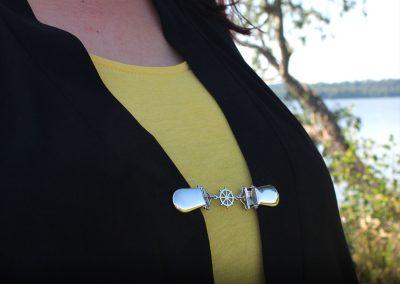 Napittoman neuletakin ja villatakin pidike nimeltä Klipsutin Ruori. Kuvassa näkyy tuote käytössä.