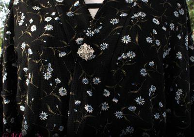Napittoman neuletakin ja villatakin pidike nimeltä Klipsutin Donna. Kuvassa näkyy tuotteen hopeanvärinen vaihtoehto käytössä. Tämän mallin kiinnitys tapahtuu magneettien avulla.