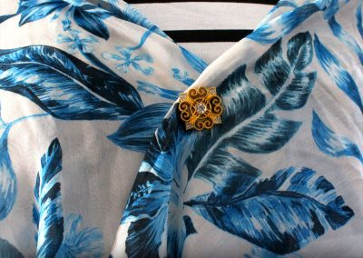 Napittoman neuletakin ja villatakin pidike nimeltä Klipsutin Donna. Kuvassa näkyy tuotteen kullanvärinen vaihtoehto käytössä. Tämän mallin kiinnitys tapahtuu magneettien avulla.