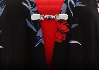 Napittoman neuletakin ja villatakin pidike nimeltä Klipsutin Giia. Kuvassa näkyy tuotteen sininen vaihtoehto käytössä.