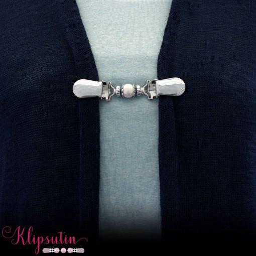 Napittoman neuletakin ja villatakin pidike nimeltä Klipsutin Giia. Kuvassa näkyy tuotteen valkoinen vaihtoehto käytössä.