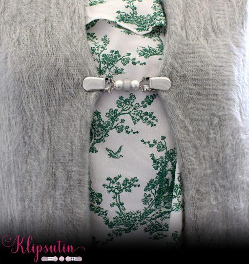 Napittoman neuletakin ja villatakin pidike nimeltä Klipsutin Tuiti. Kuvassa näkyy tuotteen harmaa vaihtoehto käytössä.