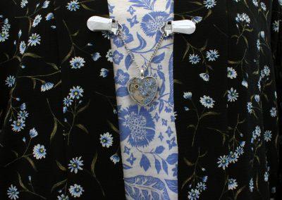 Napittoman neuletakin ja villatakin pidike nimeltä Klipsutin Rautasydän. Kuvassa näkyy tuote käytössä.