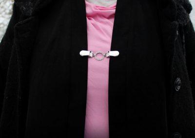 Napittoman neuletakin ja villatakin pidike nimeltä Klipsutin Ella. Kuvassa näkyy tuote käytössä.