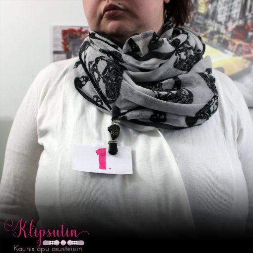 Napittoman neuletakin ja villatakin pidike nimeltä Klipsutin Wuffeli. Kuvassa näkyy tuote käytössä pystysuuntaisesti näyttelylapun pidikkeenä.