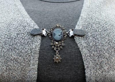 Napittoman neuletakin ja villatakin pidike nimeltä Klipsutin Lady. Kuvassa näkyy tuote käytössä.