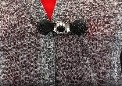 Napittoman neuletakin ja villatakin pidike nimeltä Klipsutin Olivia. Kuvassa näkyy tuote käytössä kiepautettuna toisen reunan yli.