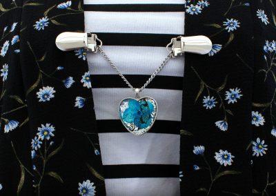 Napittoman neuletakin ja villatakin pidike nimeltä Klipsutin Kevät. Kuvassa näkyy tuotteen vaihtoehto riippuva perhonen käytössä.