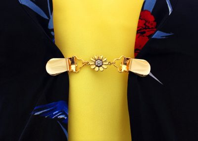 Napittoman neuletakin ja villatakin pidike nimeltä Klipsutin Sandra. Kuvassa näkyy tuote käytössä.