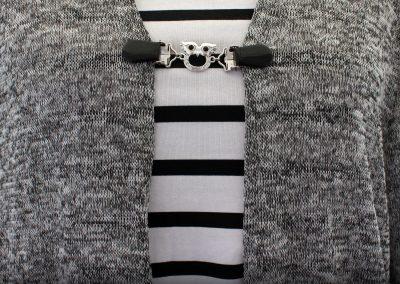 Napittoman neuletakin ja villatakin pidike nimeltä Klipsutin Pöllö. Kuvassa näkyy tuotteen musta vaihtoehto käytössä.