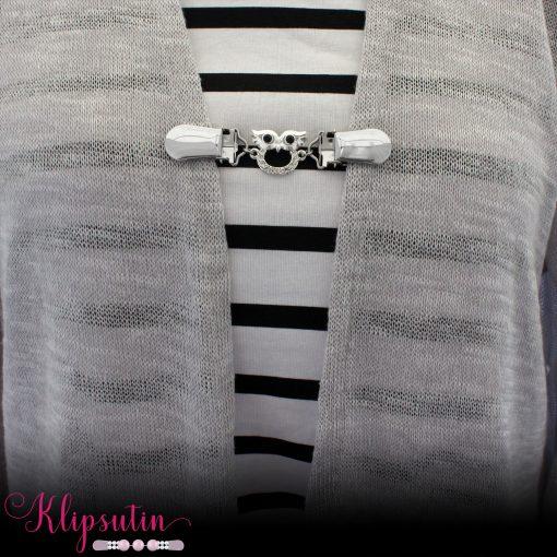 Napittoman neuletakin ja villatakin pidike nimeltä Klipsutin Pöllö. Kuvassa näkyy tuotteen hopeanvärinen vaihtoehto käytössä.