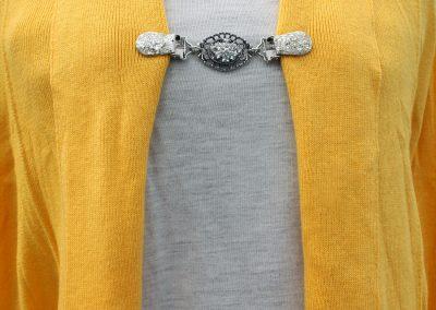 Napittoman neuletakin ja villatakin pidike nimeltä Klipsutin Blinga. Kuvassa näkyy tuote käytössä.