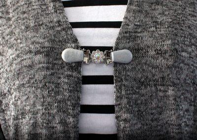 Napittoman neuletakin ja villatakin pidike nimeltä Klipsutin Daalia. Kuvassa näkyy tuote käytössä.