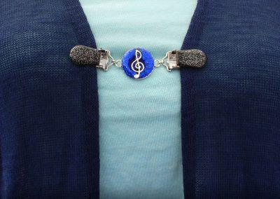 Napittoman neuletakin ja villatakin pidike nimeltä Klipsutin Sound. Kuvassa näkyy tuotteen sininen vaihtoehto käytössä.