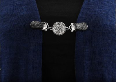 Napittoman neuletakin ja villatakin pidike nimeltä Klipsutin Sound. Kuvassa näkyy tuotteen harmaa vaihtoehto käytössä.