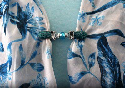 Napittoman neuletakin ja villatakin pidike nimeltä Klipsutin Salla. Kuvassa näkyy tuotteen vaihtoehto turkoosi käytössä.