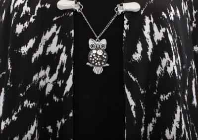 Napittoman neuletakin ja villatakin pidike nimeltä Klipsutin Aika. Kuvassa näkyy tuotteen vaihtoehto kirkas mustalla pohjalla käytössä.
