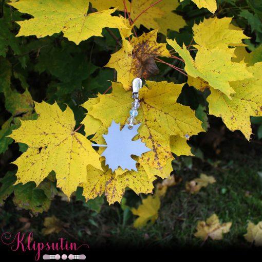 Napittoman neuletakin ja villatakin pidike nimeltä Klipsutin Heijastava Lehti. Kuvassa näkyy tuote luonnon keskellä.