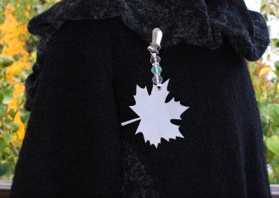 Napittoman neuletakin ja villatakin pidike nimeltä Klipsutin Heijastava Lehti. Kuvassa näkyy tuote käytössä.