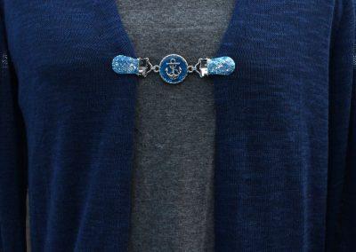 Napittoman neuletakin ja villatakin pidike nimeltä Klipsutin Ankkuri. Kuvassa näkyy tuote käytössä.