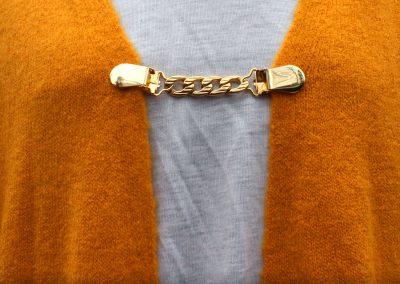 Napittoman neuletakin ja villatakin pidike nimeltä Klipsutin Kaski. Kuvassa näkyy tuotteen kullanvärinen vaihtoehto käytössä.