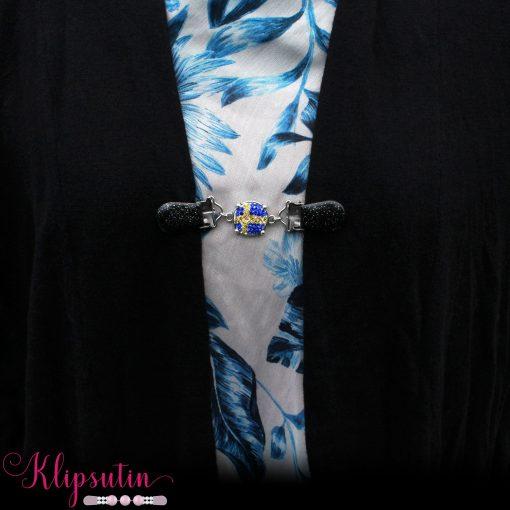 Napittoman neuletakin ja villatakin pidike nimeltä Klipsutin Lippu. Kuvassa näkyy tuotteen vaihtoehto Ruotsi käytössä.
