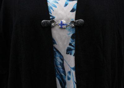 Napittoman neuletakin ja villatakin pidike nimeltä Klipsutin Lippu. Kuvassa näkyy tuotteen vaihtoehto Suomi käytössä.