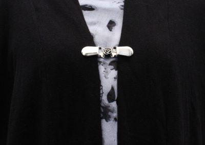 Napittoman neuletakin ja villatakin pidike nimeltä Klipsutin Pieni Ruusu. Kuvassa näkyy tuote käytössä.