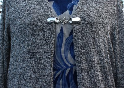 Napittoman neuletakin ja villatakin pidike nimeltä Klipsutin Ranskanlilja. Kuvassa näkyy tuote käytössä.