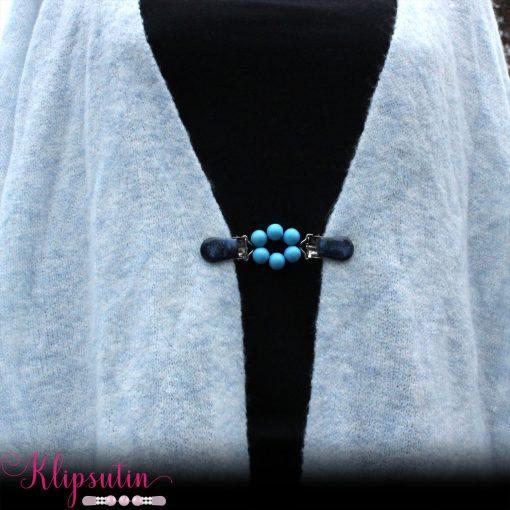 Napittoman neuletakin ja villatakin pidike nimeltä Klipsutin Ruu. Kuvassa näkyy tuotteen vaaleansininen vaihtoehto käytössä.