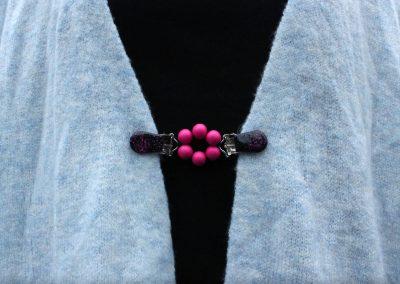 Napittoman neuletakin ja villatakin pidike nimeltä Klipsutin Ruu. Kuvassa näkyy tuotteen vaaleanpunainen vaihtoehto käytössä.