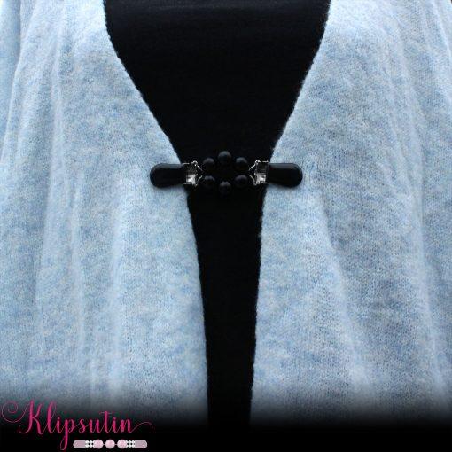 Napittoman neuletakin ja villatakin pidike nimeltä Klipsutin Ruu. Kuvassa näkyy tuotteen musta vaihtoehto käytössä.