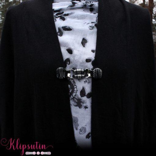 Napittoman neuletakin ja villatakin pidike nimeltä Klipsutin Sips. Kuvassa näkyy tuote käytössä.