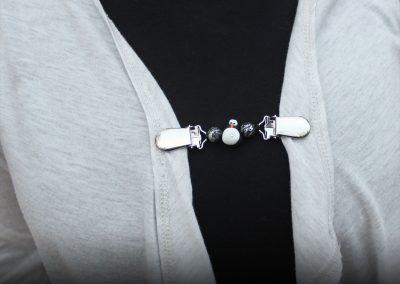 Napittoman neuletakin ja villatakin pidike nimeltä Klipsutin Blingviini. Kuvassa näkyy tuote käytössä.