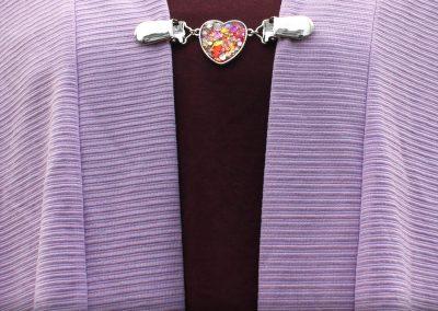 Napittoman neuletakin ja villatakin pidike nimeltä Klipsutin Rosine. Kuvassa näkyy tuote käytössä.