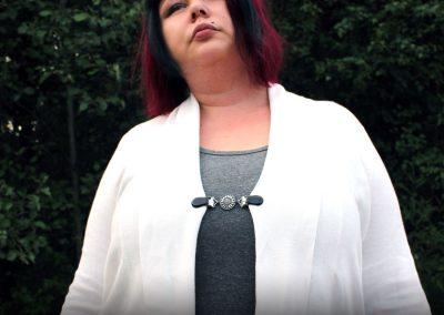 Napittoman neuletakin ja villatakin pidike nimeltä Klipsutin Sannina Black. Kuvassa näkyy tuote käytössä.