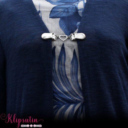 Napittoman neuletakin ja villatakin pidike nimeltä Klipsutin Sydän. Kuvassa näkyy tuote käytössä.