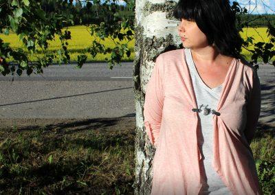 Napittoman neuletakin ja villatakin pidike nimeltä Klipsutin Raiku. Kuvassa näkyy tuote käytössä.