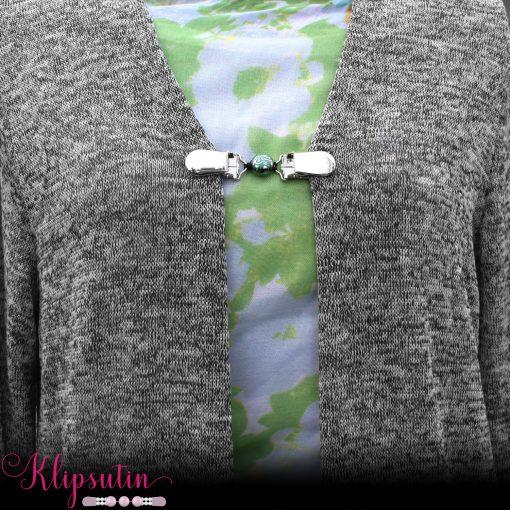 Napittoman neuletakin ja villatakin pidike nimeltä Klipsutin Mona. Kuvassa näkyy tuote käytössä.