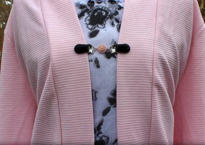 Napittoman neuletakin ja villatakin pidike nimeltä Klipsutin Elsi. Kuvassa näkyy tuote käytössä.