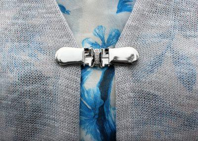 Napittoman neuletakin ja villatakin pidike nimeltä Klipsutin Sara. Kuvassa näkyy tuote käytössä.